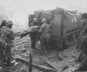 A wounded soldier is loaded into an M-3 Ambulance Halftrack, Echtz, Germany, 1944