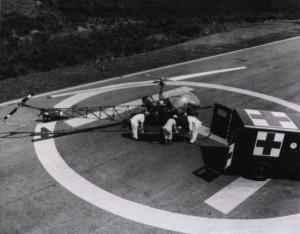 A litter patient being moved from a Bell H-13 Sioux helicopter