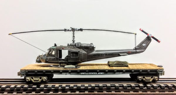 "US Army UH1C Huey Hog ""Muskets"" Helicopter w/Grenade Launcher on 50′ Flat Car, Vietnam era USAX 23075(HELI1C-FC11.2USA)_Operates on 3-Rail ""O""Gauge track"