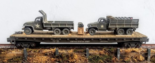 "US Army GMC 6X6 Cargo-Dump Truck w/Cab Protector & GMC 6X6 Cargo Truck w/Gas Cans on 50′ Flat Car USAX23002(MV1LMD-FC6.2USA)_Operates on 3-Rail ""O""Gauge track"
